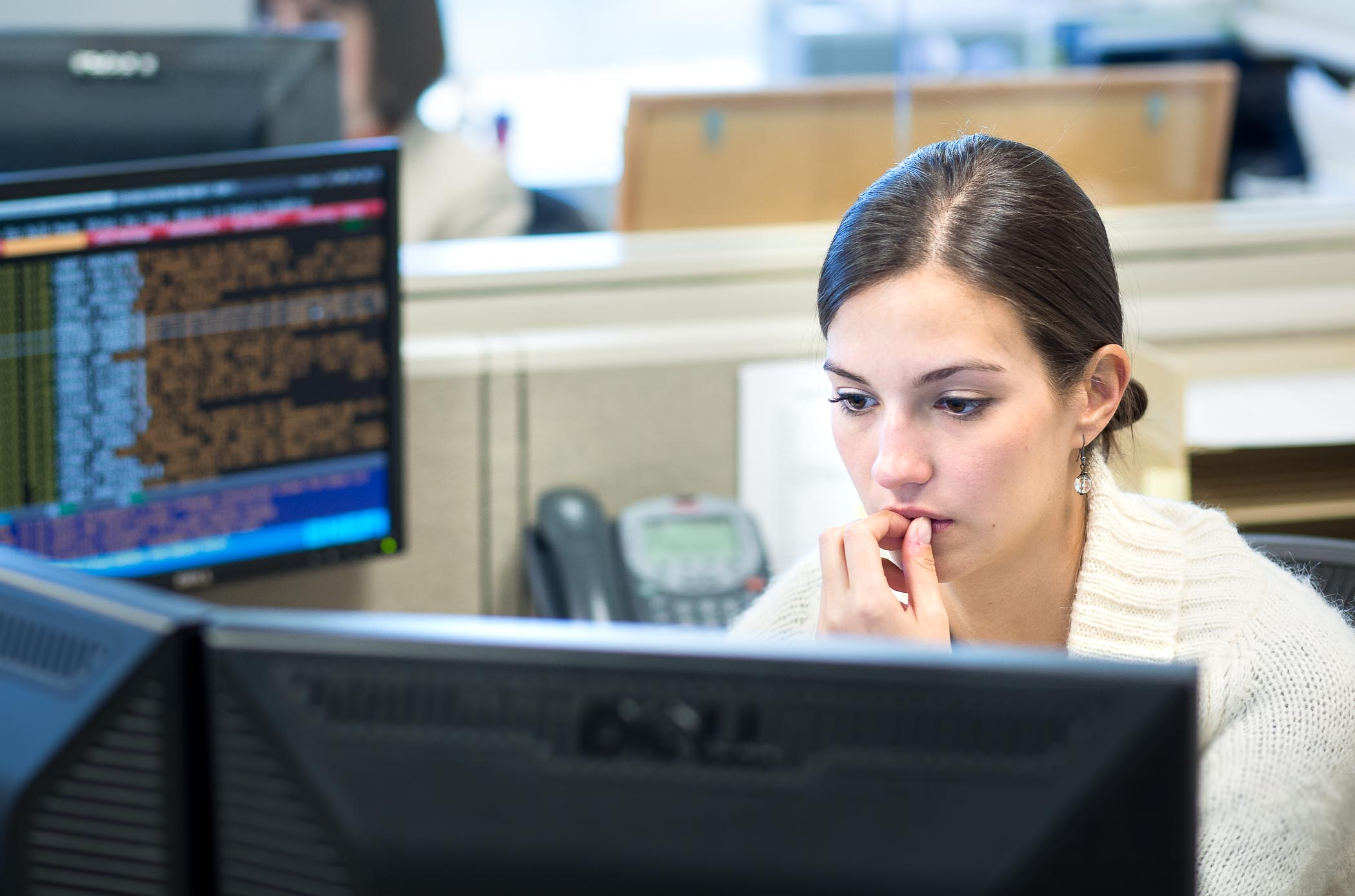 Candid photo of woman at desk reviewing stock trades by Atlanta photographer